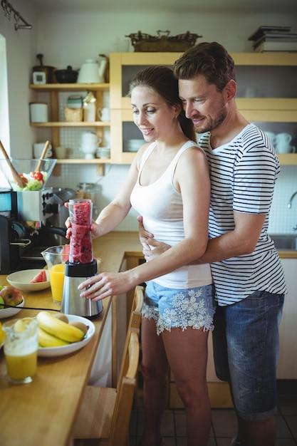 Equipaggi l'abbraccio della donna da dietro mentre preparano il frullato dell'anguria nella cucina Foto Premium