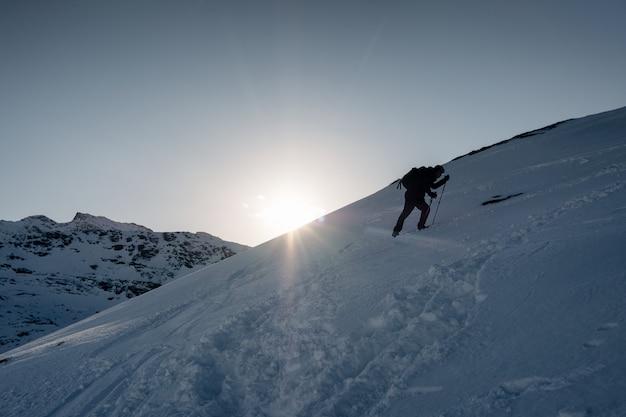 Equipaggi l'alpinista che scala sulla montagna nevosa nell'inverno al tramonto Foto Premium