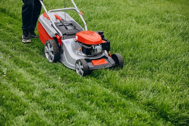Equipaggi l'erba di taglio con il motore del prato inglese nel cortile posteriore Foto Gratuite