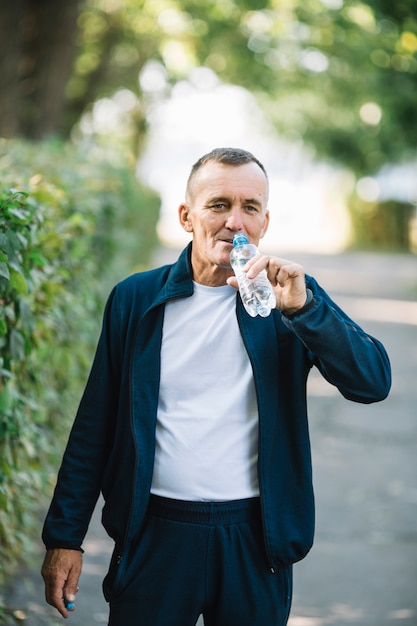 Equipaggi la bottiglia di sollevamento alla bocca per bere l'acqua Foto Gratuite