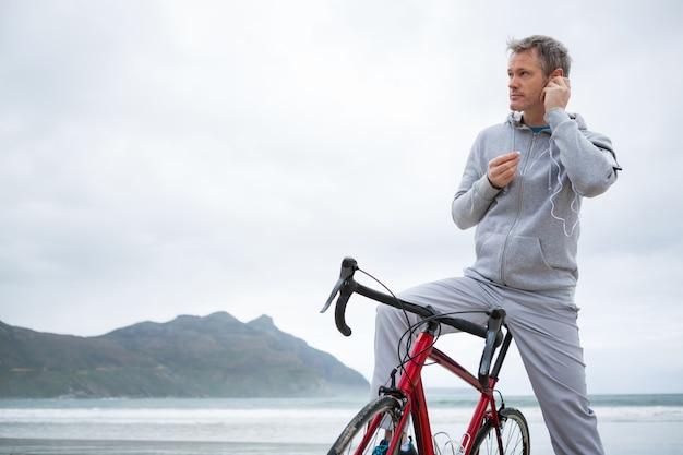 Equipaggi la condizione con la musica d'ascolto della bicicletta sulle cuffie alla spiaggia Foto Premium