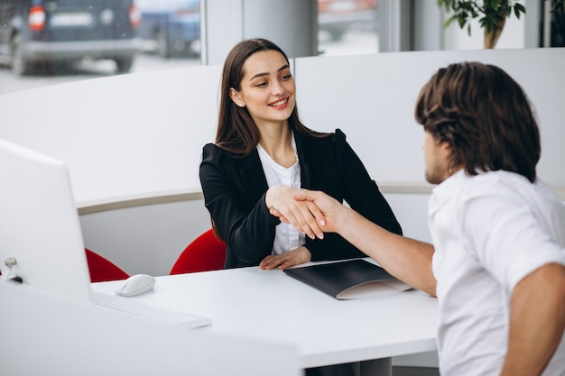 Equipaggi la conversazione con il commesso femminile in una stanza di manifestazione di automobile Foto Gratuite