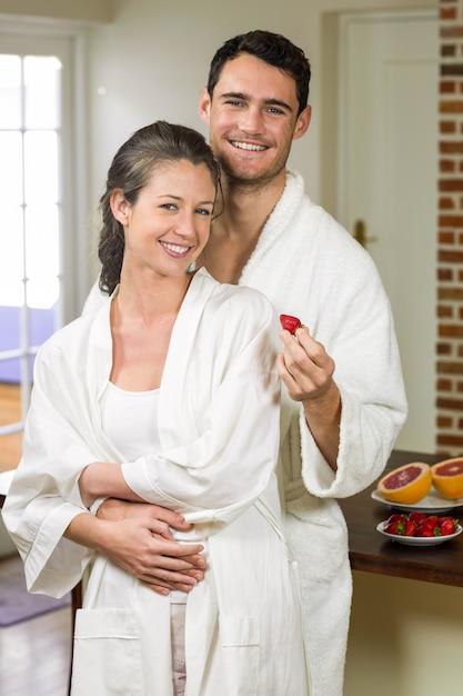 Equipaggi la fragola d'alimentazione alla donna in cucina Foto Premium