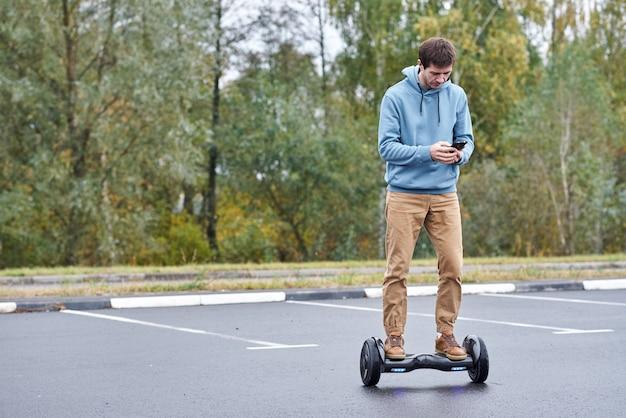Equipaggi la guida sull'hoverboard e lo smartphone all'aperto Foto Premium
