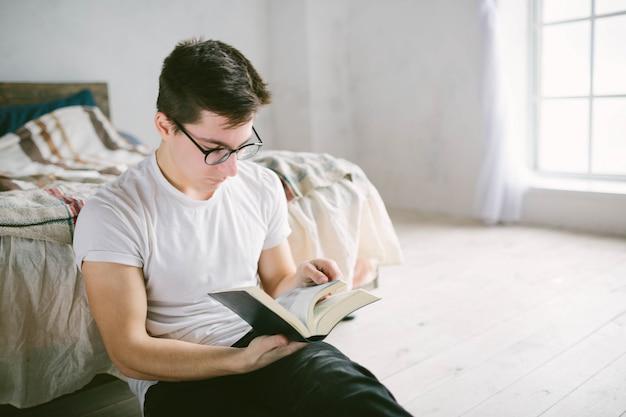 Equipaggi la lettura del libro sul suo letto a casa Foto Premium