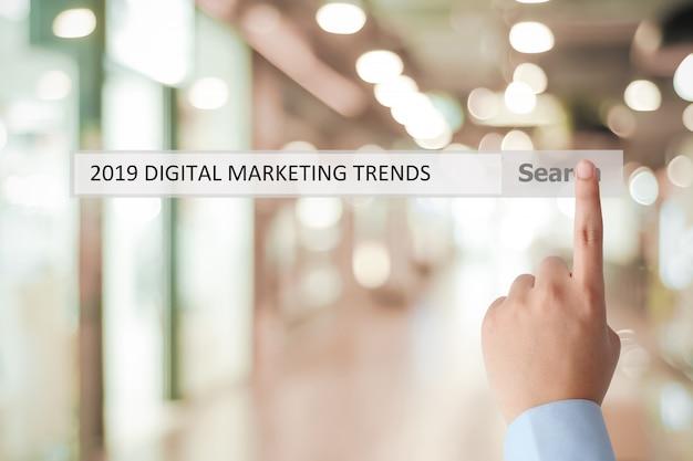 Equipaggi la mano che tocca le tendenze di vendita digitali 2019 sulla barra di ricerca sopra il fondo dell'ufficio della sfuocatura Foto Premium