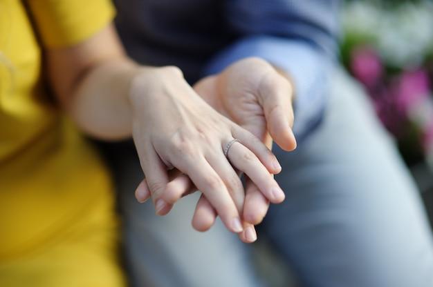 Equipaggi la mano della donna della tenuta con nozze o l'anello di fidanzamento Foto Premium
