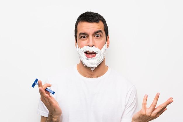Equipaggi la rasatura della sua barba sopra la parete bianca isolata che fa il gesto di dubbi Foto Premium