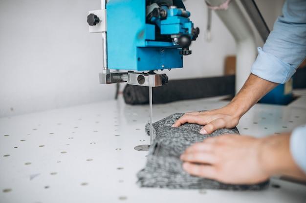 Equipaggi la taglierina ad una fabbrica di cucito, le mani maschii si chiudono su Foto Gratuite