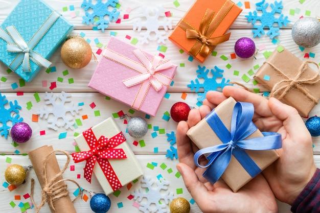 Equipaggi la tenuta del contenitore di regalo sulle decorazioni di natale Foto Premium