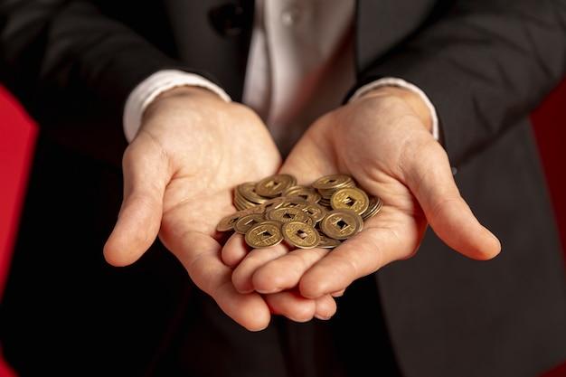 Equipaggi la tenuta delle monete cinesi dorate in mani per il nuovo anno cinese Foto Gratuite
