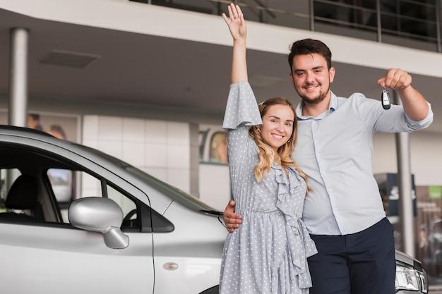 Equipaggi le chiavi e la donna dell'automobile della tenuta che sollevano la sua mano Foto Gratuite