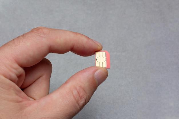 Equipaggi le dita che tengono la micro carta sim delle dita su fondo grigio con lo spazio della copia Foto Premium