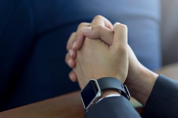 Equipaggi le mani che pregano su una bibbia santa in chiesa per il concetto di fede, la spiritualità e la religione cristiana. Foto Premium