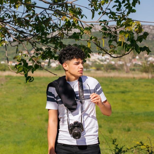 Equipaggi lo spettacolo della tenuta con la macchina fotografica intorno al suo collo che osserva via Foto Gratuite