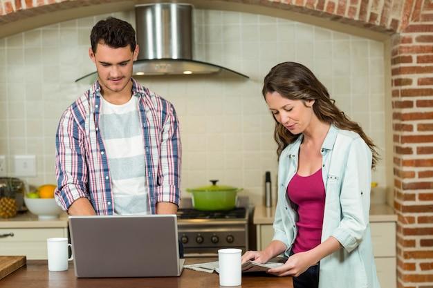 Equipaggi usando il giornale della lettura della donna e del computer portatile sul worktop della cucina Foto Premium