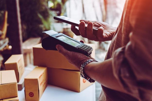 Equipaggia la macchina dei soldi di tecnologia del lettore di nfc della carta di credito della tenuta della mano dell'uomo. Foto Premium