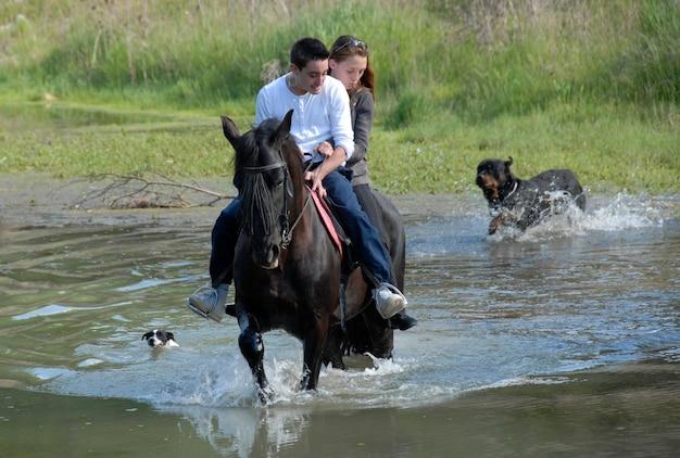 Equitazione coppia in un fiume con i cani Foto Premium
