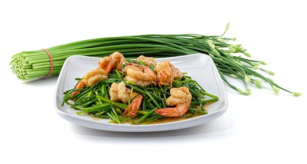 Erba cipollina cinese di fioritura in padella con i gamberetti in piatto isolato su bianco Foto Premium
