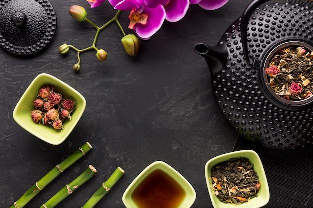 Erba del tè con il fiore e il bambù dell'orchidea sulla superficie del nero Foto Gratuite