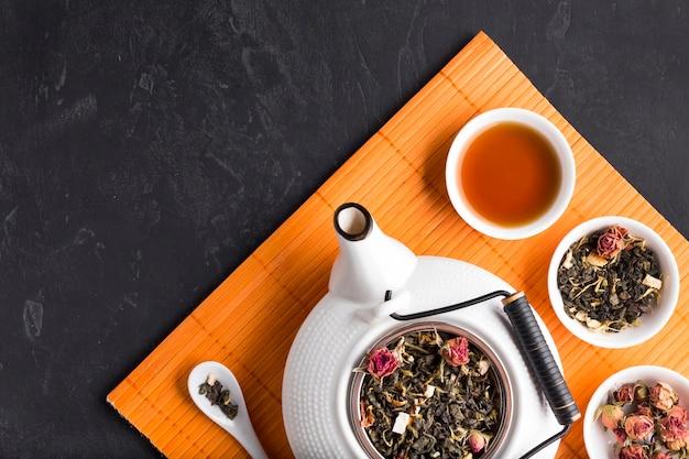 Erba e teiera secche organiche sane del tè su placemat arancio sopra fondo nero Foto Gratuite