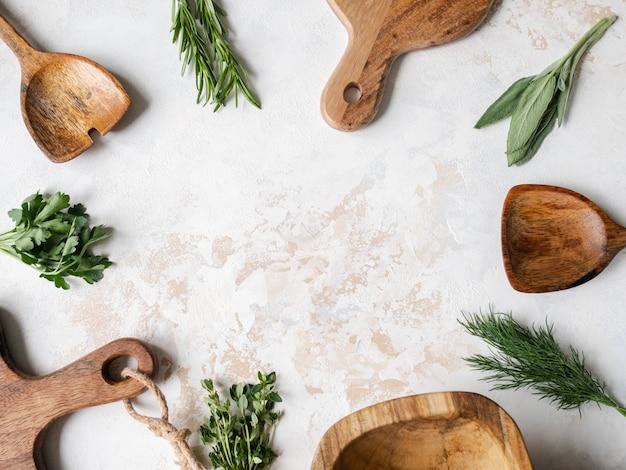 Erbe crude fresche e cucina in legno erano cornice su uno sfondo con texture. vista dall'alto, copia spazio. Foto Premium