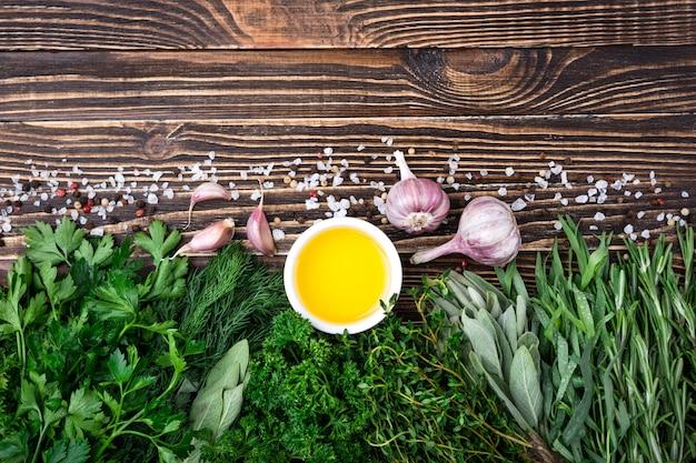 Erbe e spezie fresche, aglio, olio d'oliva su vecchio fondo di legno Foto Premium