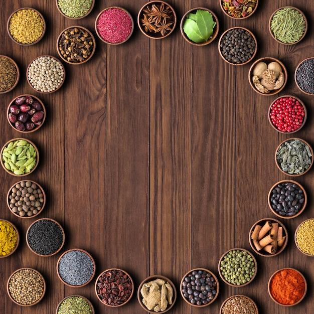 Erbe e spezie su sfondo tavolo in legno. mari multicolori Foto Premium