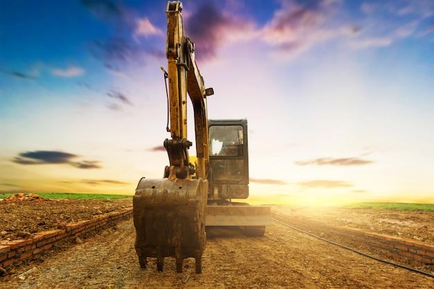 Escavatore in cantiere sul cielo al tramonto Foto Premium