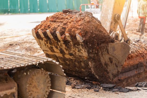 Escavatore sporco del cantiere dell'escavatore a cucchiaia rovescia con scavo di lavoro di scavatura del terreno terrestre in servizio per il tubo Foto Premium