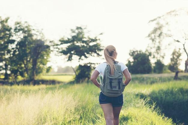 Escursionismo donna con lo zaino che cammina su una strada sterrata Foto Gratuite