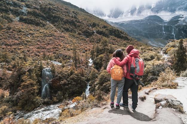 Escursionismo giovane coppia viaggiatore alla ricerca di un bellissimo paesaggio a yading nature reserve Foto Premium