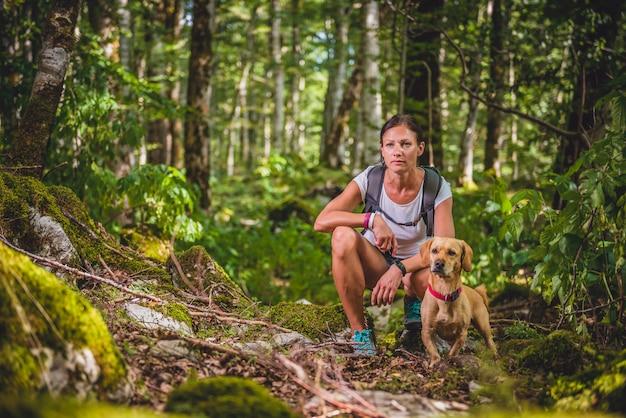 Escursionista con un cane nella foresta Foto Premium