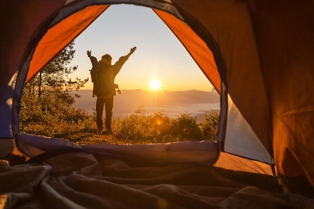 Escursionista stand al campeggio davanti tenda arancione e zaino in montagna Foto Gratuite