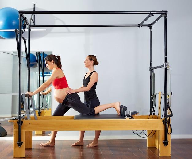 Esercitazione della cadillac del riformatore dei pilates della donna incinta Foto Premium