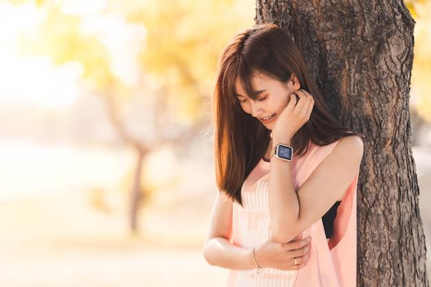 Esercitazione di rilassamento della bella giovane donna asiatica in parco Foto Premium