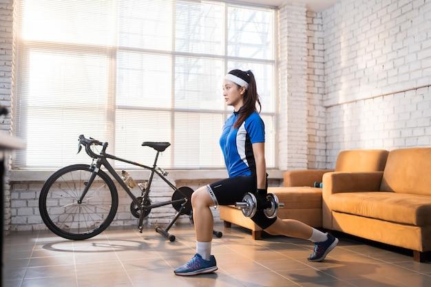 Esercizio ciclistico con affondi alle gambe. lei è a casa. Foto Premium
