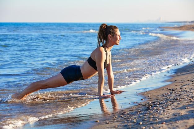 Esercizio di allenamento di yoga di pilates all'aperto sulla spiaggia Foto Premium