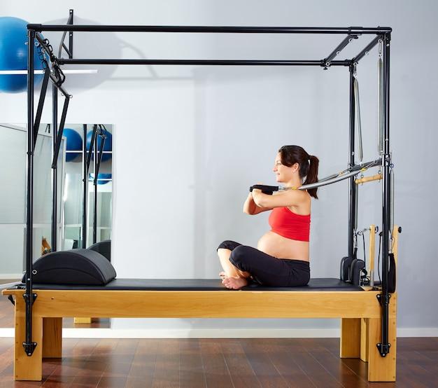 Esercizio di braccia di reformer pilates donna incinta Foto Premium