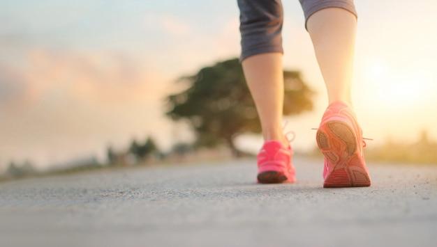 Esercizio di camminata della donna dell'atleta sulla strada rurale nel fondo di tramonto Foto Premium
