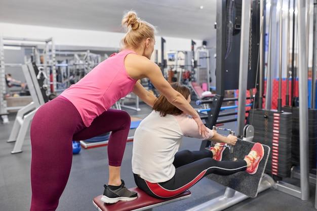 Esercizio di lavoro dell'istruttore personale di forma fisica con la donna matura in palestra Foto Premium