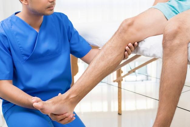 Esercizio di riabilitazione di addestramento del fisioterapista al paziente con gamba rotta Foto Premium