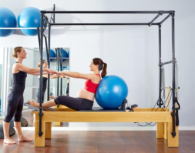 Esercizio fitball del riformatore dei pilates della donna incinta Foto Premium