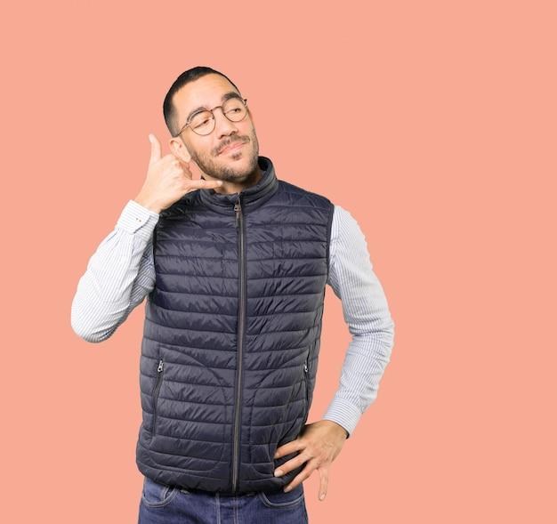 Esitante giovane che fa un gesto di chiamata con la mano Foto Premium