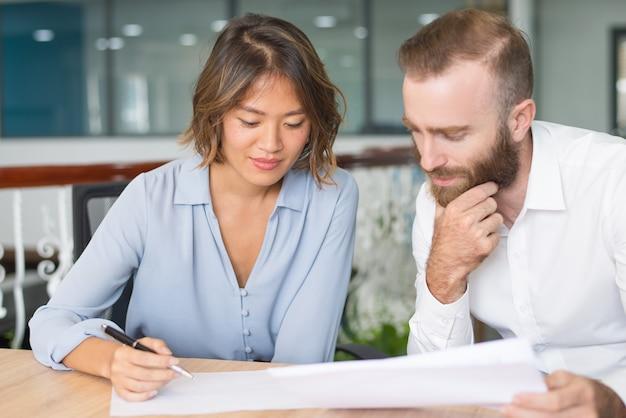 Esperti di affari pensierosi analizzando report di marketing Foto Gratuite