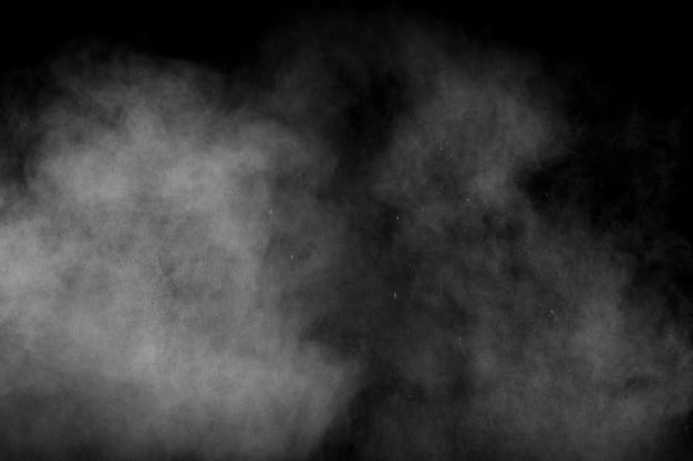 Esplosione astratta di polvere bianca su sfondo nero. la polvere bianca espira nell'aria. Foto Premium