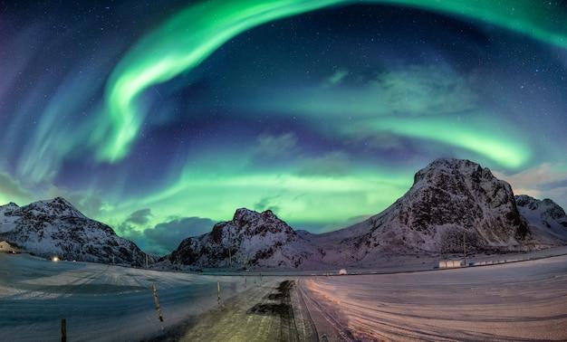 Esplosione di aurora boreale su catena montuosa innevata Foto Premium