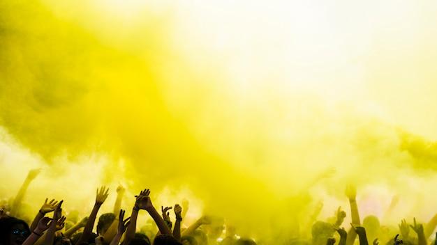 Esplosione di colore giallo holi sulla folla Foto Gratuite