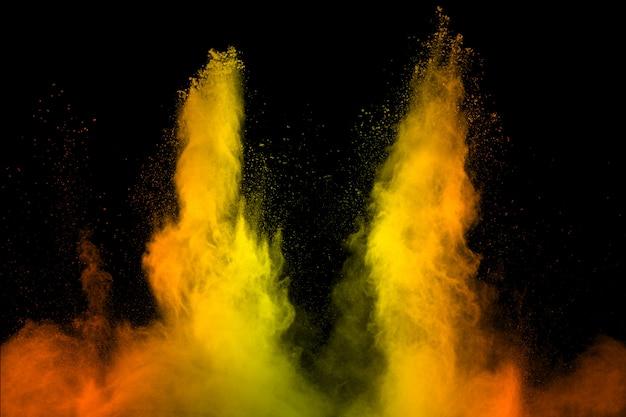 Esplosione di particelle di polvere giallo arancione su sfondo nero. Foto Premium