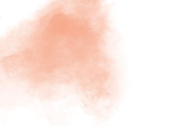 Esplosione di polvere arancione-chiaro astratta su priorità bassa bianca. bloccare il movimento di schizzi di particelle di polvere arancione chiaro. Foto Premium